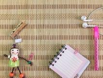笔记投入了有桃红色颜色笔、玩偶、服装扣子和耳机的席子 库存图片