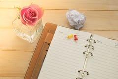 笔记本、别针和桃红色玫瑰在玻璃花瓶在木背景 免版税库存图片