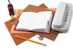 笔记本、卷尺和白色电话在织地不很细纸 库存图片