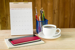 笔记本、咖啡杯和堆与日历的书在木t 图库摄影