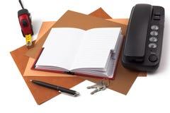 笔记本、圆珠笔和电话在织地不很细纸 库存照片