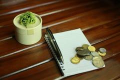 笔记本、在木背景和装饰隔绝的笔、硬币 库存照片