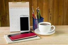 笔记本、巧妙的电话、咖啡杯和堆与日历的书 库存图片