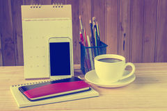 笔记本、巧妙的电话、咖啡杯和堆与日历的书 免版税库存照片