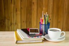 笔记本、巧妙的电话、咖啡杯和堆在木选项的书 免版税图库摄影
