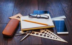 笔记本、文具、绘图工具和一些块玻璃顶视图  即兴创作 免版税库存图片