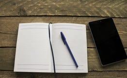 笔记本、片剂和笔在一张老木书桌上 在视图之上 免版税图库摄影