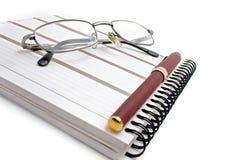 笔记本、玻璃和笔 免版税库存照片