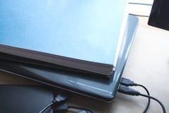 笔记本、硬盘和纸垫在木背景 免版税库存照片
