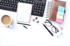 笔记本、笔、键盘和在一张白色书桌安置的咖啡杯在t 免版税库存图片