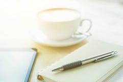 笔记本、笔和咖啡在木桌上的 图库摄影
