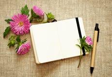 笔记本、笔和翠菊 库存照片