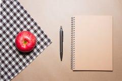 笔记本、笔和苹果在棕色桌上镶边了织品和包装纸背景 免版税库存图片