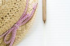 笔记本、笔和草帽有一把桃红色弓的 免版税库存照片