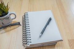 笔记本、笔和玻璃在木板 图库摄影