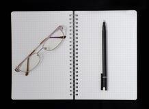 笔记本、笔和玻璃 图库摄影
