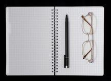 笔记本、笔和玻璃 库存图片