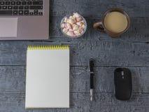 笔记本、笔记本、笔、咖啡杯和蛋白软糖在黑暗的木桌上 图库摄影