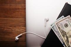 笔记本、耳机、日志和美元在木桌上 事务 库存图片