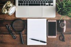 笔记本、膝上型计算机、放大镜、照相机、电话和时钟在一张木桌上 免版税库存照片
