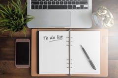 笔记本、膝上型计算机、时钟、智能手机和学报在与要做名单词的一张木桌上 免版税库存图片