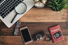 笔记本、膝上型计算机、智能手机、指南针、护照、时钟和照相机在木桌背景 图库摄影