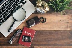 笔记本、膝上型计算机、智能手机、指南针、护照、时钟和照相机在木桌背景 库存照片
