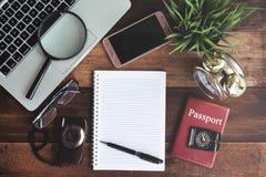 笔记本、膝上型计算机、智能手机、指南针、护照、时钟和照相机在木桌背景 免版税库存图片