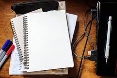 笔记本、膝上型计算机和铅笔,在古色古香的木工作表上 库存图片