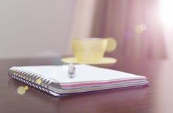 笔记本、钢笔和黄色在桌上与阳光 免版税库存照片