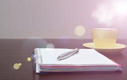 笔记本、钢笔和黄色在桌上与阳光 免版税库存图片
