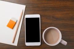笔记本、铅笔、橡皮擦、电话和热的饮料在木书桌上 免版税图库摄影