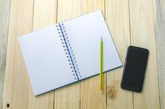 笔记本、铅笔和巧妙的电话在木桌工作区 免版税库存照片