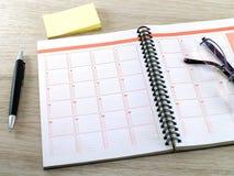 笔记本、镜片、笔和黄色空白的稠粘的笔记关于木桌地板 免版税库存图片