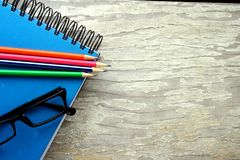 笔记本、镜片和五颜六色的铅笔 免版税库存图片