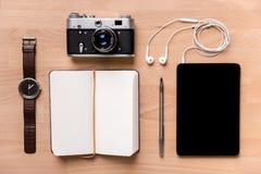 笔记本、黑屏片剂有耳机的,照相机、手表和笔 免版税库存照片