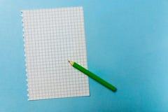 笔记本和一支绿色铅笔在蓝色背景 办公室解决主题的问题情形 免版税图库摄影