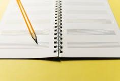 笔记本和一支绿色铅笔在黄色背景 办公室解决主题的问题情形 库存图片