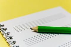 笔记本和一支绿色铅笔在黄色背景 办公室解决主题的问题情形 库存照片