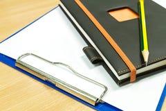 笔记本和剪贴板有白纸的在办公室桌上 免版税库存图片