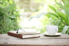 笔记本和咖啡在木桌上 免版税库存照片