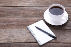 笔记本和咖啡在灰色木背景的 免版税库存照片
