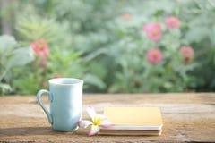 笔记本和咖啡在蓝色杯子在木桌上 库存图片