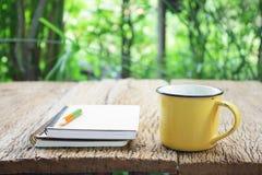 笔记本和咖啡在黄色杯子在木桌上 免版税库存图片