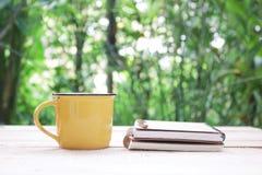 笔记本和咖啡在黄色杯子在木桌上 库存照片