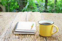 笔记本和咖啡在黄色杯子在木桌上 免版税图库摄影