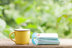 笔记本和咖啡在黄色杯子在木桌上 免版税库存照片