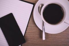 笔记本和咖啡杯在木表面葡萄酒减速火箭的过滤器 免版税库存图片
