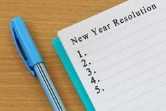 笔记本和新年决议文本在棕色wo被安置 免版税库存照片