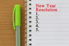 笔记本和新年决议文本在棕色wo被安置 免版税库存图片